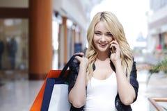 Winkelende vrouw die op de telefoon spreken Stock Fotografie