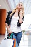Winkelende vrouw die op de telefoon spreken Stock Foto's