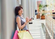 Winkelende vrouw die telefoon met behulp van Stock Foto