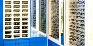 winkelglazen Tribune met glazen in de geschiedenis van optica Grote selectie van verschillende glazen royalty-vrije stock afbeeldingen