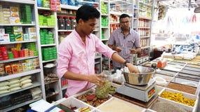 Winkelier het Verkopen bij Kruidmarkt Stock Foto's