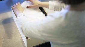 Winkelmedewerker die een witte sjaal in een doos en met droge bloemen zetten stock video