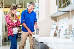 Winkelmedewerker in ijzerhandel adviserende klant over lavat royalty-vrije stock afbeelding