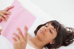 Winkeln Sie Schuß einer jungen Frau, die ein Buch liest Stockbild