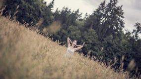 Winkelsicht über die Frau, die im Grasland nahe Holz sitzt Stockbilder