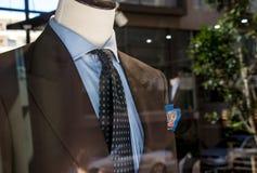 Winkelvenster van de kleermakerswinkel die van mensen een ledenpop in een bruin gemaakt kostuum en een blauwe band tonen stock foto