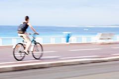 Winken Sie den unscharfen Radfahrer zu, der schnell auf einen Stadtradweg geht Lizenzfreies Stockfoto