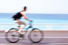 Winken Sie den unscharfen Radfahrer zu, der schnell auf einen Stadtradweg geht Stockfotos