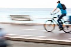 Winken Sie den unscharfen Radfahrer zu, der schnell auf einen Stadtradweg geht Lizenzfreie Stockbilder
