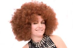 Winking. Pretty woman with red afro wig winking Royalty Free Stock Images