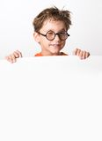 Winking. Cute lad winking through glasses while standing behind white partition Stock Photography