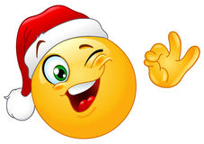Winking emoticon with Santa hat. Winking emoticon wearing Santa hat Vector Illustration