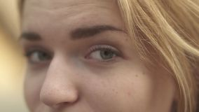 Winking eyes of a girl close up. Pretty girl raises eyebrows up several time and then smiles in camera. Woman turns her head away. The girl raises eyebrows up stock footage