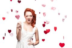 Winking red-haired woman holding lollipop Stock Photo
