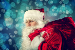 Winking Santa Claus carries a bag with gifts. Royalty Free Stock Photo