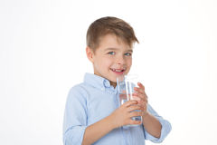 Winking sly child. Little boy drinks water with glass Stock Photos