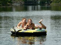 Winking Teen Best Friends. My teenage daughter and her friend relaxing on a tube (and posing) on a lazy ride down the river behind our boat on a beautiful sunny Stock Photo