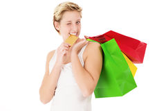 Winking woman bites on her credit card Royalty Free Stock Photography
