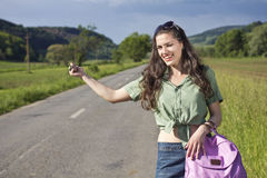 Winking woman hitchhiking, portrait Stock Images