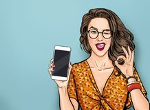 Winking Woman In Glasses Showing Smart Pone And OK Sign. Pop Art Girl Holding Phone. Digital Advertisement Female Model Stock Photography