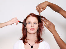 Winking Woman Makeover. Portrait of a redheaded woman winking as one set of hands styles her hair, and another hand applies her makeup. Taken in studio; isolated stock image