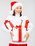 Winking woman in santa hat with many gift boxes Royalty Free Stock Images