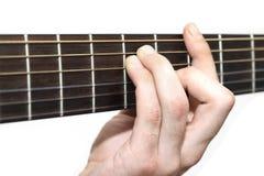 Winklig, einen Gitarrenakkord spielend lizenzfreies stockbild