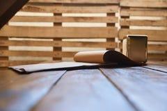 Winkliger Schuss des weißen leeren Lebensmittels oder der Getränkekarte auf hölzernem Klippbrett auf rustikalem Holztisch Lizenzfreies Stockfoto