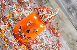 Winkliges furchtsames orange Kürbisglas auf rustikalem Holz Stockfotografie