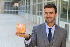 Winky businessman using piggybank to save money.  Stock Photo
