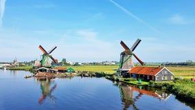 Winmills por um lago em Zaanse Schans, os Países Baixos Fotografia de Stock Royalty Free