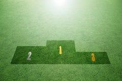 Winnaarpodium op heldergroen gras stock afbeeldingen