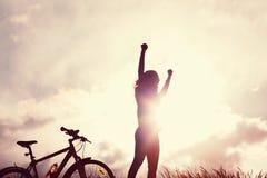 Winnend meisje met fietssilhouet stock afbeeldingen