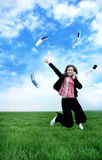 Winner. Woman jumping on a green field with mobile phones around her