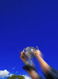 Winner. Trophy thrust to a Blue sky with motion Blur royalty free stock photos