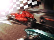 The winner. At the end of a F1 race, a red car crosses first the finish line under a big checkered flag, as its pilot raises the finger towards the sky in sign