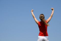 The winner. Energetic young woman with her arms raised in joy Royalty Free Stock Photos