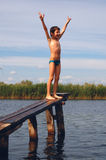 The winner. Boy on the narrow wooden pier with his hands up with the body and face expression of the winner Royalty Free Stock Images