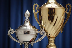 Winner award cups : gold and silver signs. Gold and silver cups on a background of dark blue cloth royalty free stock photography
