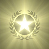 Winner badge star and olive leaf light flare. A shiny five points star pentacle surrounded by olive leafs shining with powerful light flares. Winner award Royalty Free Stock Photo