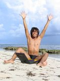 Winner on beach. Asian boy on tropical beach with laptop, cheering with arms high: concept of winner Stock Photos