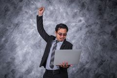Winner business man holding laptop with arms raised. Young winner business man holding laptop with arms raised Stock Image