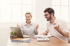 Young happy business partners in office. Winner business partners happy, in white modern office, sitting at workplace. Colleagues raising their arms celebrating Stock Photo