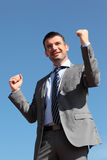Winner businessman. Beautiful businessman standing up in blue sky stock image