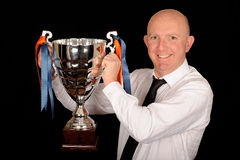 Winner Businessman. Holding a trophy, on a black studio background Royalty Free Stock Photography