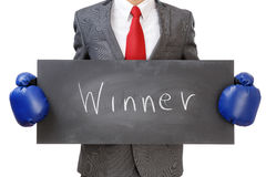 Winner. Businessman in boxing gloves holding sign winner. Isolated on white background Stock Photos