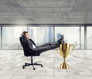 Winner businessman relaxing over a golden cup royalty free stock photo