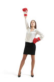 Winner businesswoman. In formal wear and red gloves raising one hand up and looking with confidence at camera. isolated on white background Stock Photos