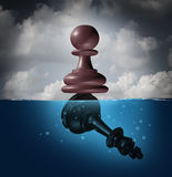 Winner And Champion. Success concept as a chess pawn piece standing on top of a drowning king as a business metaphor for victory and defeat Stock Photography