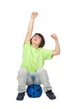 Winner child sitting on blue soccer ball Royalty Free Stock Image